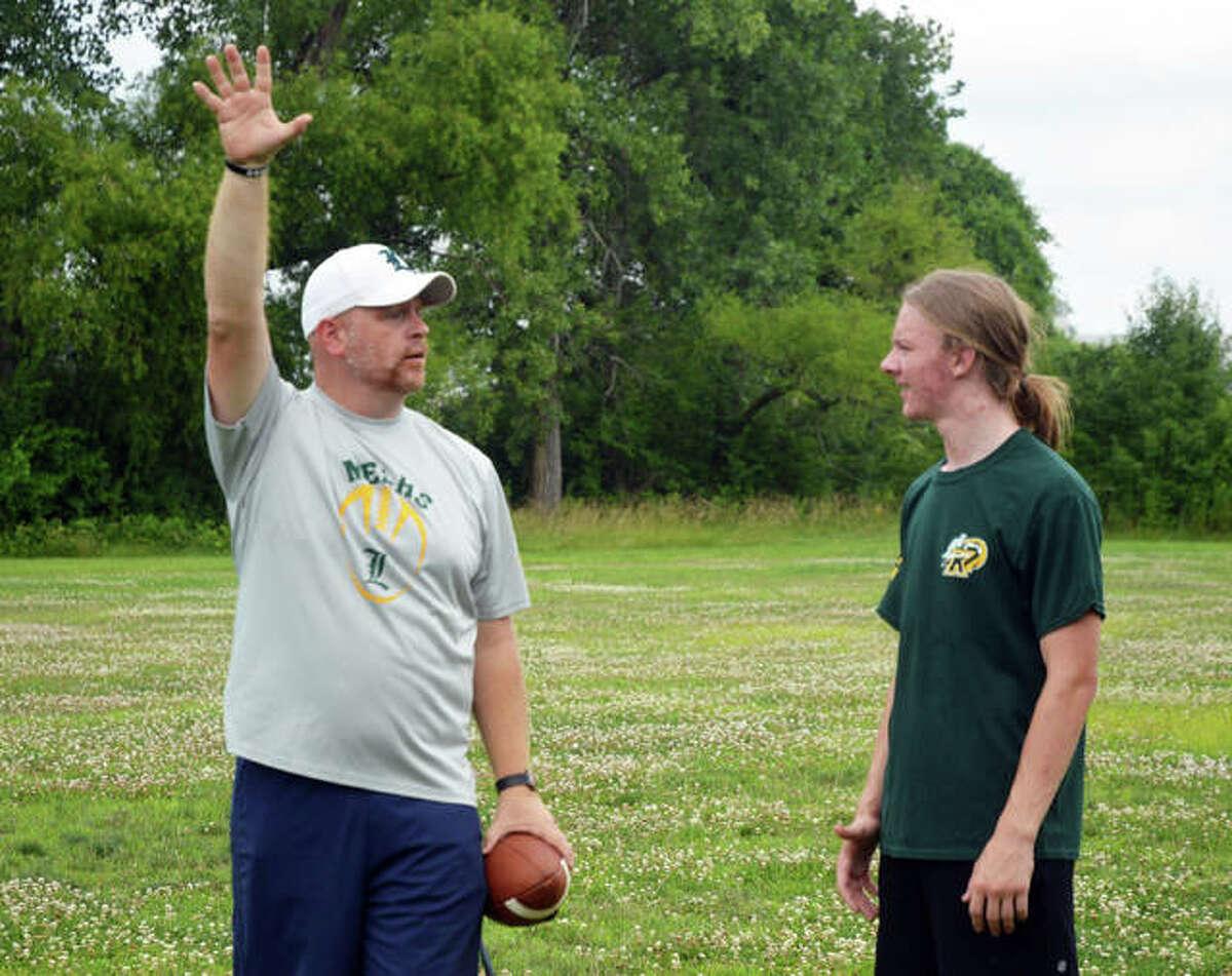 Metro-East Lutheran football coach Mike Koch, left, talks to senior Kaiden Downs during a practice session at MELHS last week.