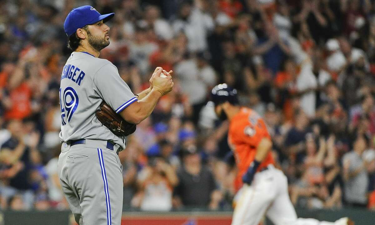 In this Aug. 4, 2017 file photo, Toronto Blue Jays relief pitcher Mike Bolsinger, left, walks off the mound as Houston Astros' Marwin Gonzalez rounds the bases after hitting a three-run home run during the fourth inning of a baseball game in Houston. Bolsinger sued the Astros, claiming their sign-stealing scheme contributed to a poor relief appearance that essentially ended his big league career.