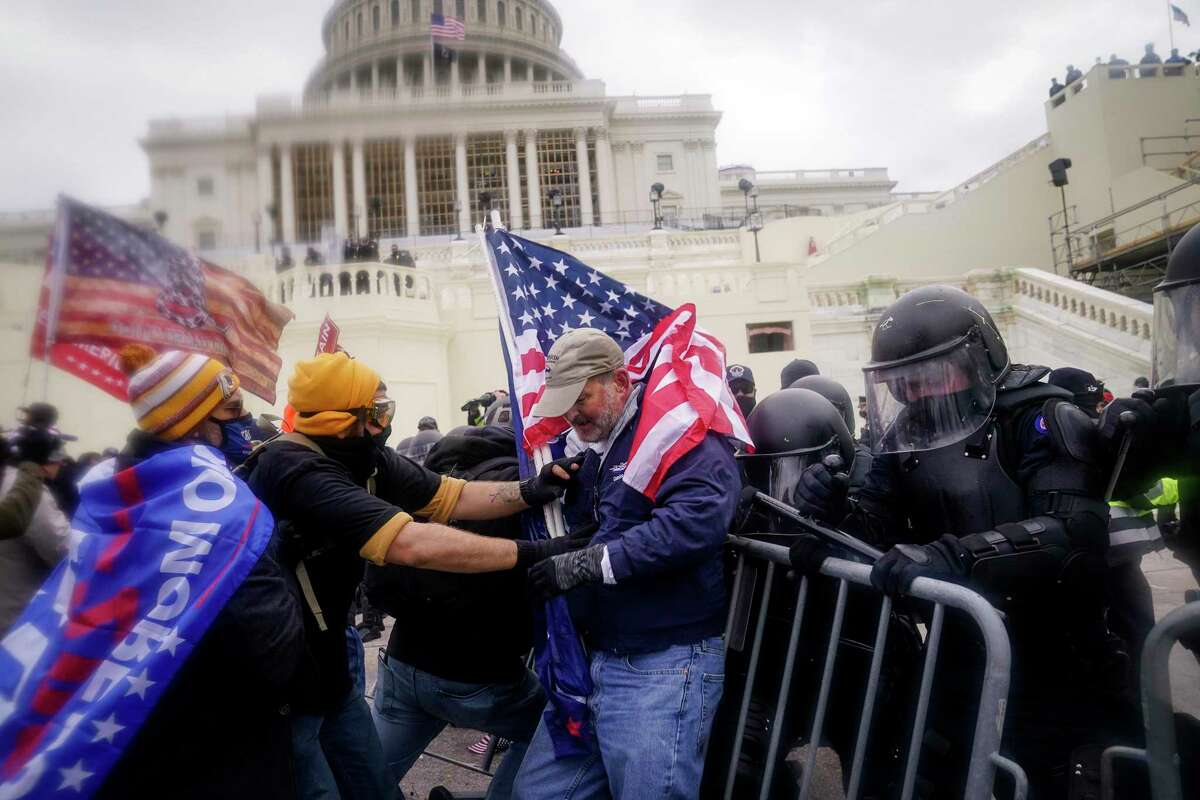 """FILE - Rioters try to break through a police barrier at the Capitol on Jan. 6, 2021, in Washington. Former President Donald Trump is falsely describing the circumstances of Ashli Babbitt's death as he foments conspiracy theories about the siege of the Capitol on Jan. 6 and all the """"love in the air"""" that day. (AP Photo/John Minchillo, File)"""