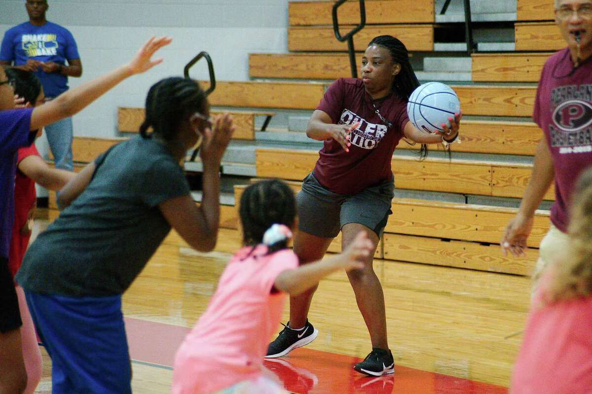 Pearland first-year head basketball coach Jere Adams leads an agility drill at the Pearland summer girls basketball camp.