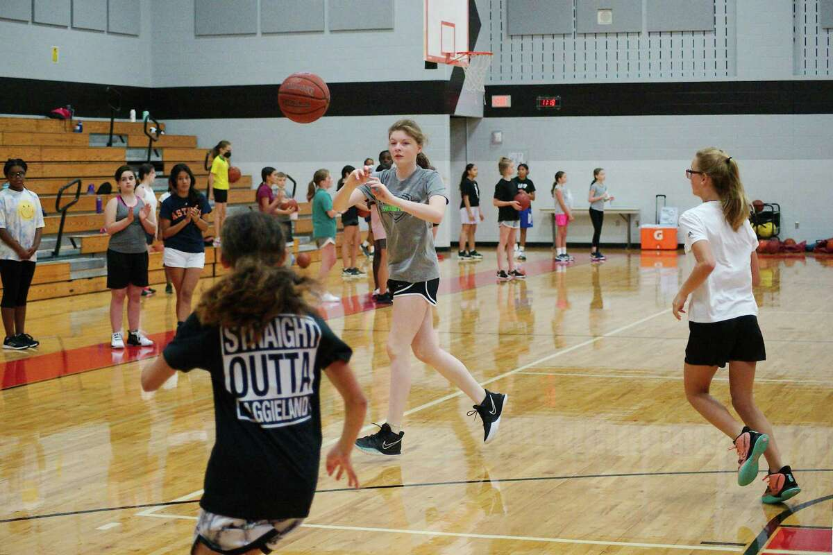 Thalia Cantu, Savanah Epting and Presley Buckmaster participate in a passing drill at the Pearland summer girls basketball camp.