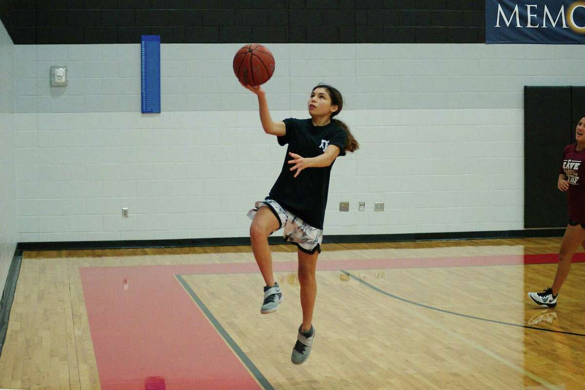 Thalia Cantu lays up a shot during a drill at the Pearland summer girls basketball camp.