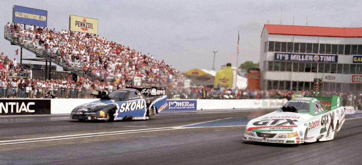 Funny car driver John Force at right gets his 100th career win against Tommy Johnson Jr. in the finals the NHRA O'Reilly Nationals at Houston Raceway Park in Baytown in 2002.