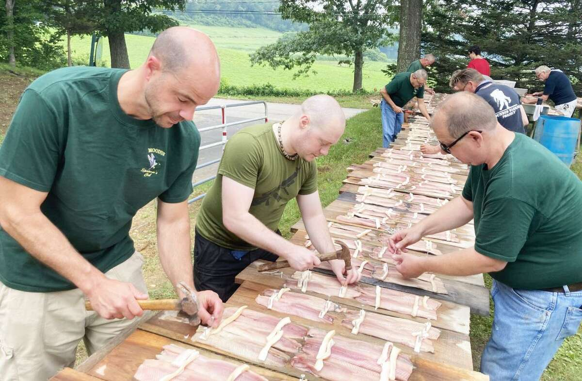 Moodus Sportsmen's members Brad Thody, Alex Gerhart, and Chip Houska nail salt pork strips to hold the filet of shad onto planks at the annual shad bake July 11 in East Haddam.