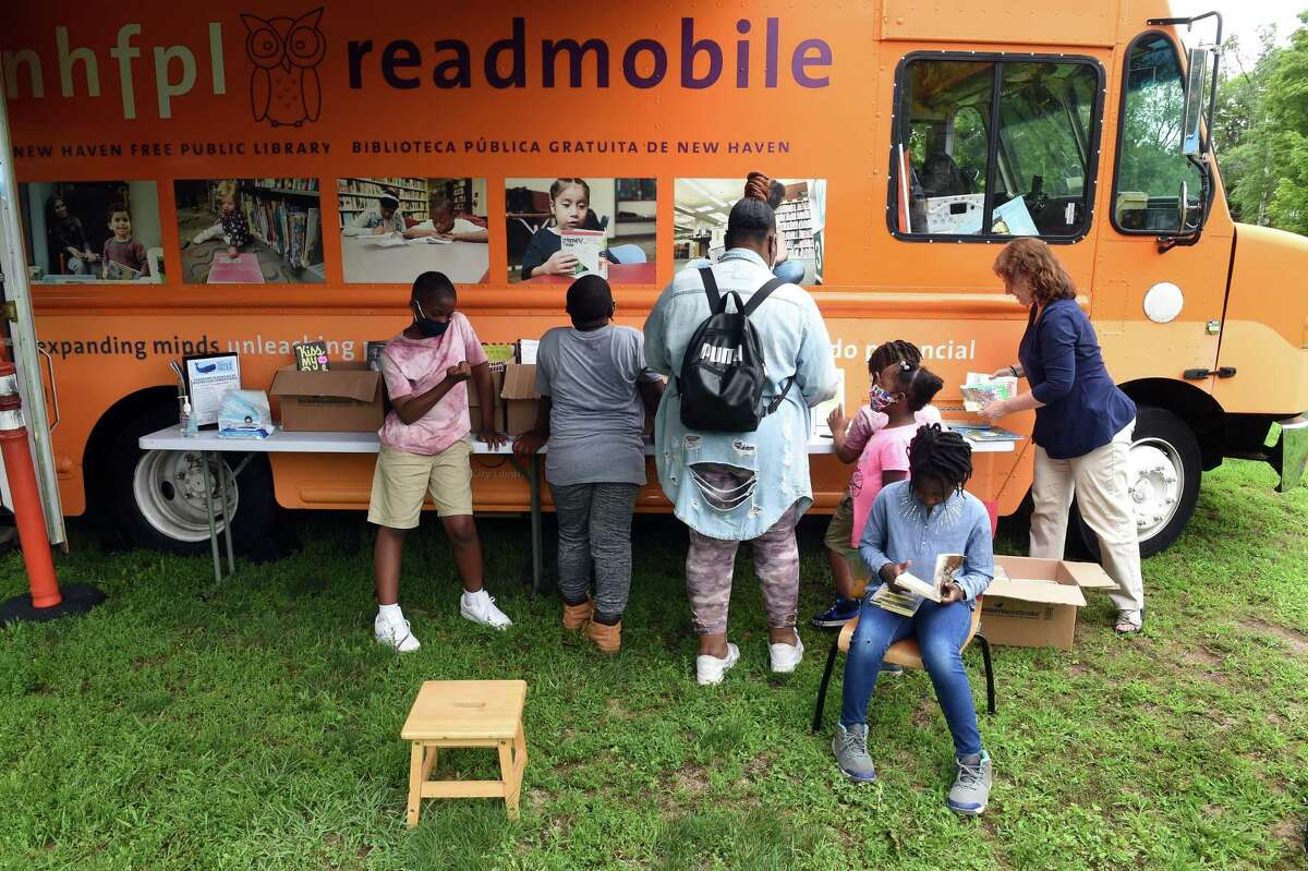 Mamah Cisse, right, 8, of New Haven reads a book in front of the New Haven Free Public Library Readmobile during the New Haven Public Schools 2021 Superintendent's Reading and Fitness Challenge at Scantlebury Park in New Haven July 13, 2021.