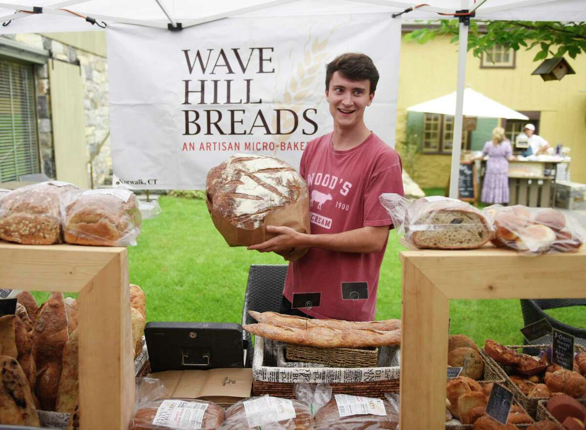 Andrew Santacroce holds a huge sourdough loaf at the Norwalk-based Wave Hill Bread stand at the Tavern Garden Market at the Greenwich Historical Society in the Cos Cob section of Greenwich, Conn. Wednesday, July 14, 2021. On alternating Wednesdays from May through November, vendors sell a variety of market items such as produce, sweets, bread, gifts, crafts, and flowers. The market is held outdoors in the garden when weather permits, and indoors in the lobby when it rains.