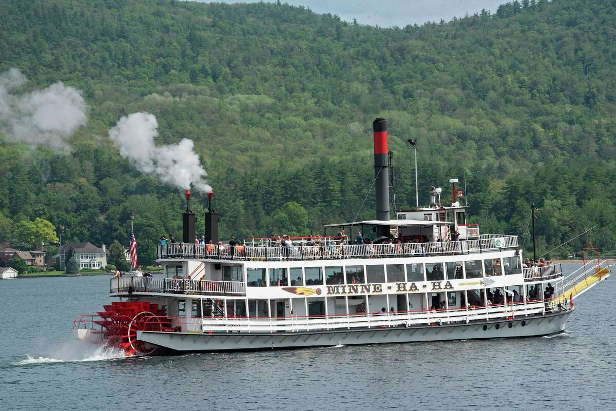 People are seen enjoying a cruise on the Minne-Ha-Ha paddlewheel boat earlier this month. The fifth reported harmful algal bloom documented on the lake, and the first one reported this season, was recently discovered near Million Dollar Beach. (Lori Van Buren/Times Union)