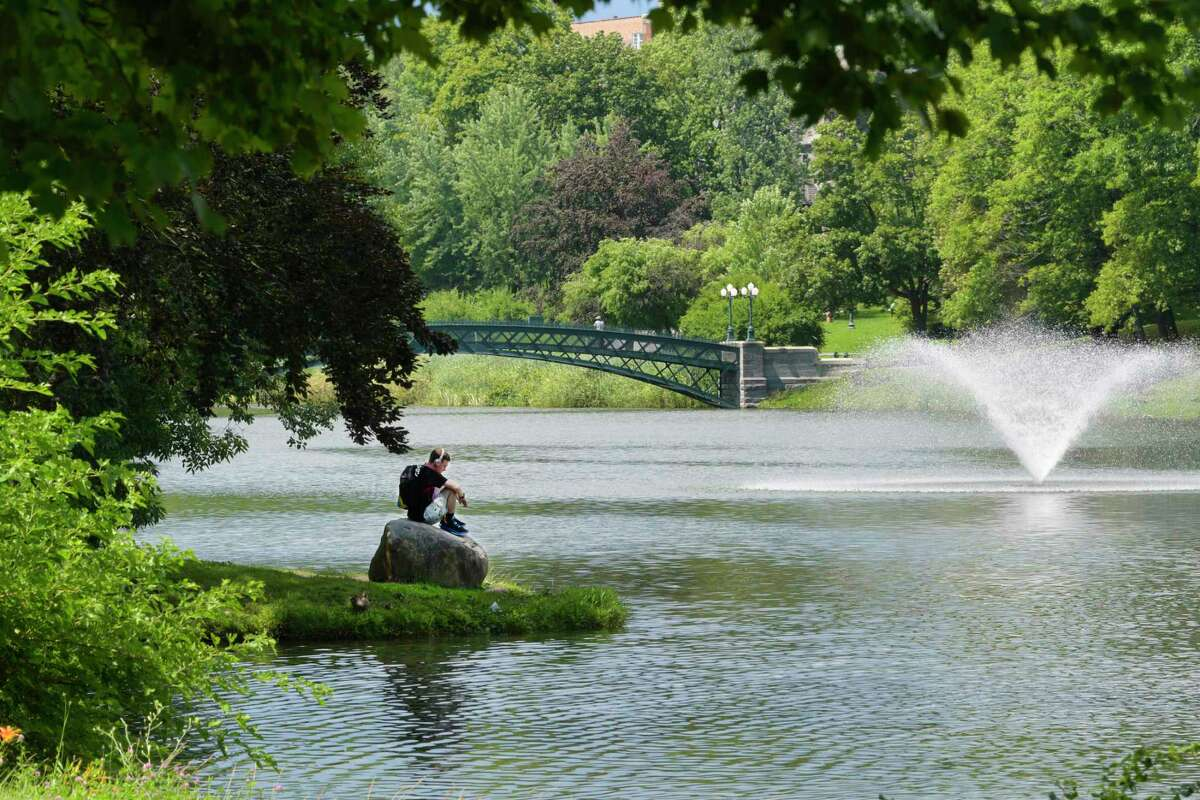 Corey Chiaro of Albany listens to music as he sits on a rock near the lake in Washington Park on Wednesday, July 14, 2021, in Albany, N.Y. (Paul Buckowski/Times Union)