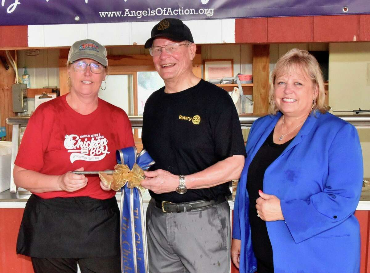 Big Rapids Rotary Club president David Nichols (center) with Big Rapids Rotarian Michelle Moen (right) hand over the keys to the chicken barbecue booth at the Mecosta County Fair to Angels of Action co-founder Joni-Thompson (left) during a ceremony this week. (Joe Crew/For the Pioneer)