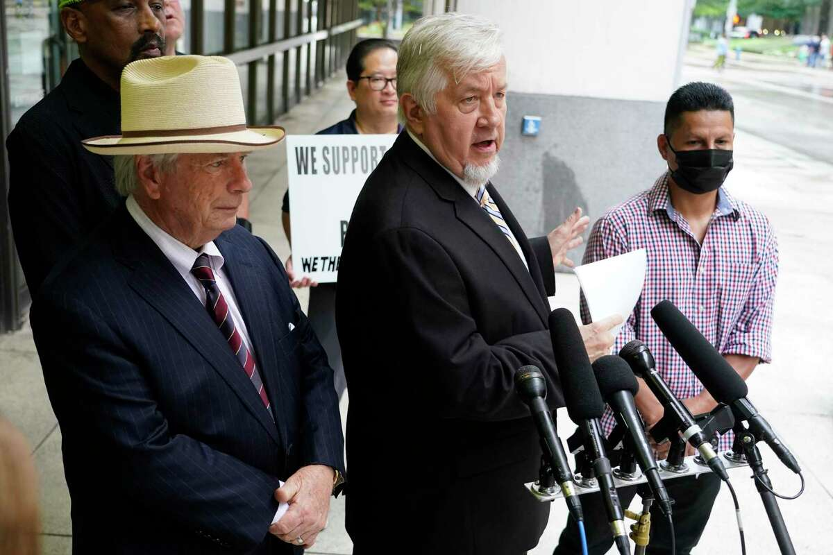 Attorneys Mike DeGeurin, left, and Randall Kallinen, center, and their client Jose Gomez, right, are shown at a press conference held outside the Houston Police Dept., 1200 Travis, Wednesday, July 14, 2021 in Houston. The press conference was about the federal civil rights verdict against a former HPD officer and a current officer stemming from a 2017 traffic stop of their client Jose Gomez.