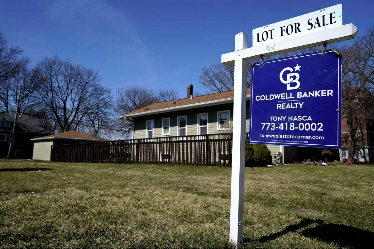 """FILE - A """"lot for sale"""" sign stands along side a housing lot in Des Plaines, Ill., Sunday, March 21, 2021."""