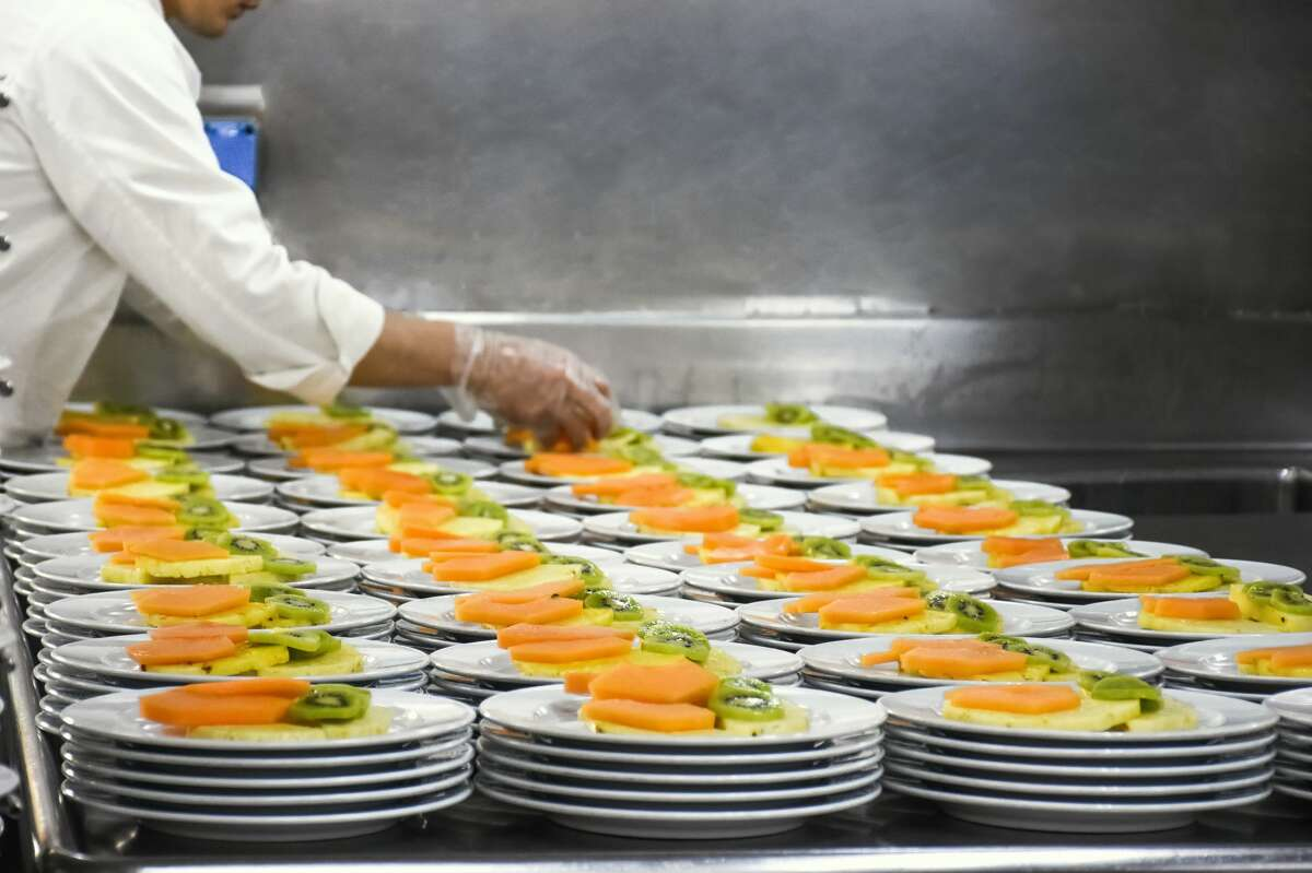 Professional chef preparing 200 fruit salad portions as part of a fine dining restaurant menu in a generic location