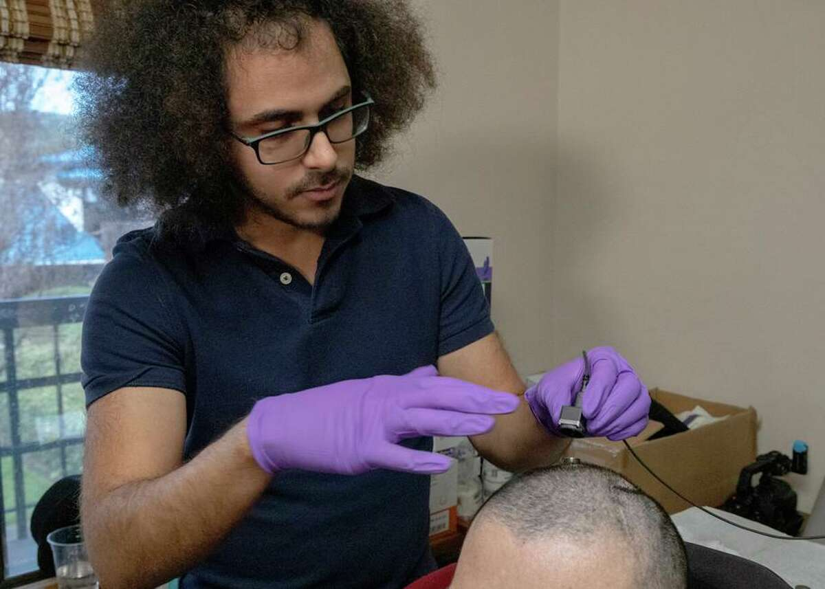 David Moses works with a paralyzed man whose brain signals are being recorded and translated into words. The signals are recorded with an electrode panel implanted on the surface of the man's brain, then transmitted by cable to a computer.