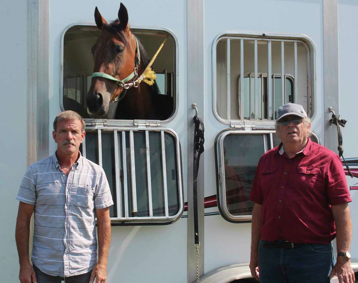 Dan Hoffman, left, and Randy McConnell pose with their horse, Secret Stash,prior to Wednesday's grandstand race event at the Mecosta County Fair. (Pioneer photo/Joe Judd)