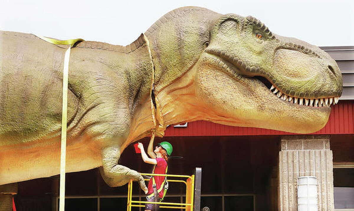 William Scalf, an employee of Dino Stroll, stitches up the seams in the animatronic tyrannosaurus rex being setup Wednesday outside the Gateway Convention Center in Collinsville. The center will host Dino Stroll, an exhibit of more than 70-life-like reptiles and life from the Mesozoic Era, this weekend on July 17-18. T-Rex will move his tail, arms and head.
