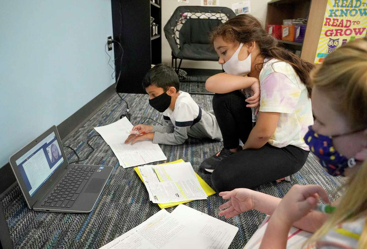 Third graders Niam Patel, 8, left, Jennifer Rosa, 8, and Kelli Blair, 9, right, participate in a virtual session with A&M senior Grace Neal during their class at Grand Oaks Elementary School in Tomball earlier this year.