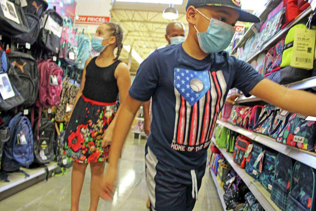 Fort Bend ISD fourth-grader Ronald Reynolds III (right) and twin sister Reagan (left) shop for back to school supplies at the H-E-B location in Sienna with their dad, State Rep. Ron Reynolds last year.