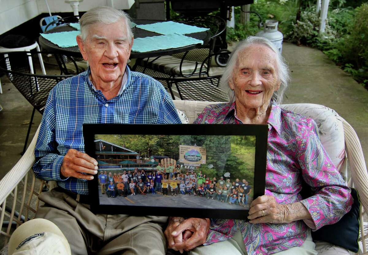 Holding up a photo of a recent family reunion, James Knick sits with his wife Alice as he celebrates his 99th birthday as well as their 77th wedding anniversary together at their home in Fairfield, Conn., on Sunday June 27, 2021. The Knicks have 11 children, 26 grandchildren and 16 great-grandchildren.