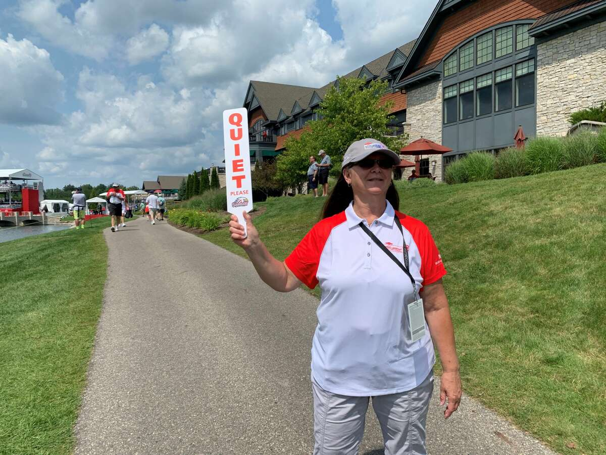 Volunteer Debbie Shepherd of Hemlock signals for spectators to be quiet as players prepare to tee off on the 18th hole during Wednesday's first round of the Dow Great Lakes Bay Invitational at the Midland Country Club, July 14, 2021.