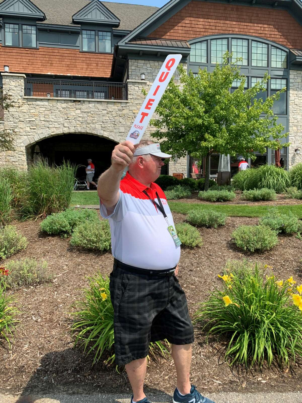 Volunteer Pat Murtha of Tawas City signals for spectators to be quiet as players prepare to tee off on the 18th hole during Wednesday's first round of the Dow Great Lakes Bay Invitational at the Midland Country Club, July 14, 2021.