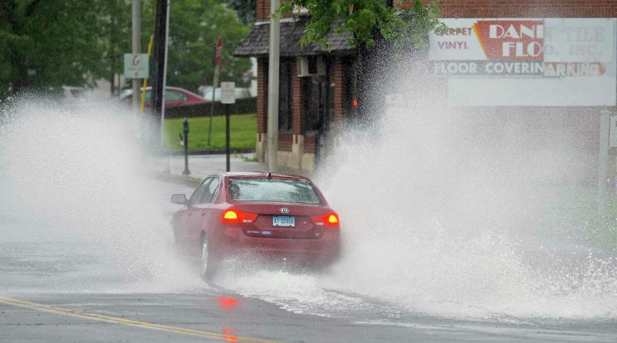 A car splashes through water on Main Street in Danbury. Part of the street was blocked off because of water from Tropical Storm Elsa.