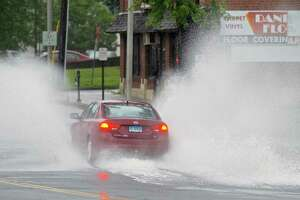 A car splashes through water across Main Street by Main Street Park on Friday. Part of Main Street was blocked off because of water from tropical storm Elsa's rain. Danbury, Ct, on Friday, July 9, 2021.