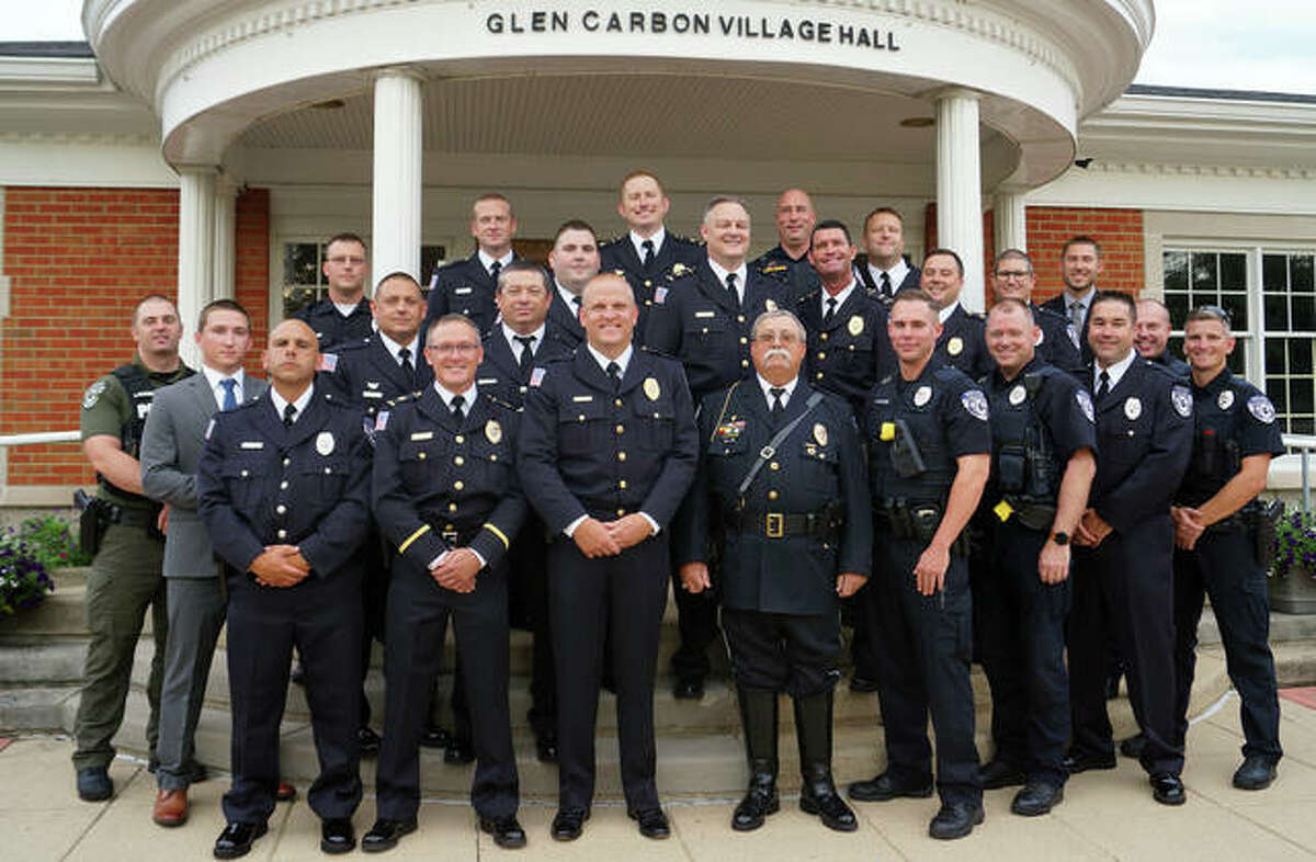 """The Glen Carbon Police Department turned out in force for three of their own Tuesday, as retired sergeant James """"Sarge"""" Jones, front row center, flanked by new Sgt. Steven Deist to his left, and the village's newest police officer, Aaron Porter, on his right. Jones's retirement was recognized, Deist was promoted and Porter was sworn in, respectively. Four former village police officers attended the meeting, including one from Minnesota."""