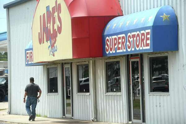 Members of the DEA, ATF, and other law enforcement agencies investigate during a raid at Jake's Fireworks Super Store and surrounding warehouses Wednesday in Nederland. Several employees were detained inside as the raid continued before eventually being released. One man was handcuffed and taken into custody. Photo taken Wednesday, July 15, 2020 Kim Brent/The Enterprise