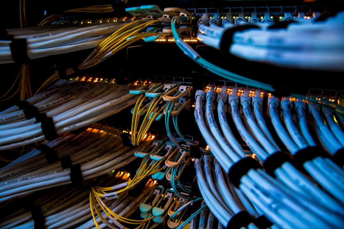 Fiber-optic cables, center, and copper Ethernet cables feed into switches inside a communications room at an office in London.