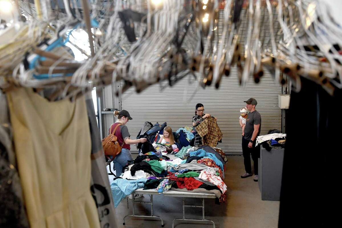 """A family shops during the last of a two-day clothing swap held at The Art Studio, Inc. Those lookinng to clear out their closets while getting some """"new to you"""" items. Photo made Wednesday, July 14, 2021 Kim Brent/The Enterprise"""