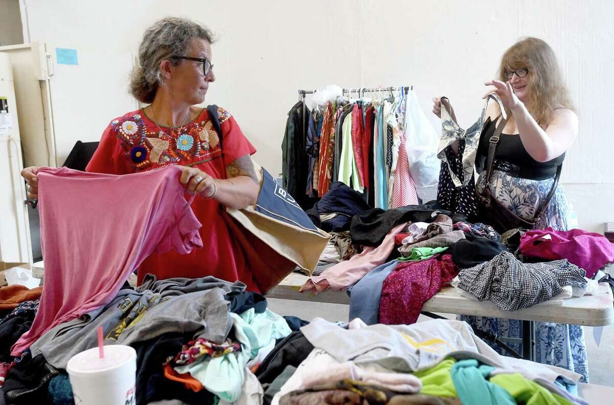"""Kimberly Brown looks back. as she and Kristen Whitmire look through available items after dropping off their donations during the last of a two-day clothing swap held at The Art Studio, Inc. Those lookinng to clear out their closets while getting some """"new to you"""" items. Photo made Wednesday, July 14, 2021 Kim Brent/The Enterprise"""
