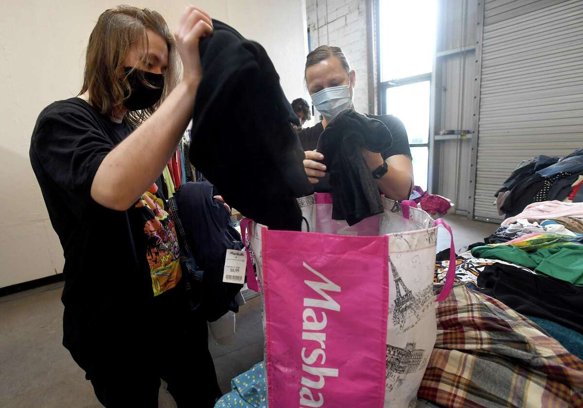 """Samuel and Tisha Kulovitz unload their items to donate before shopping during the last of a two-day clothing swap held at The Art Studio, Inc. Those lookinng to clear out their closets while getting some """"new to you"""" items. Photo made Wednesday, July 14, 2021 Kim Brent/The Enterprise"""