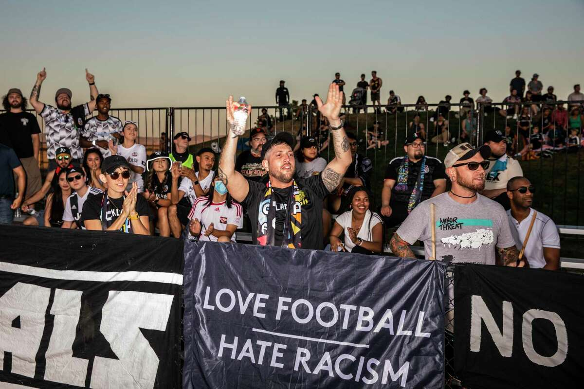 Robin Banks, center, and Mike P. with the Oakland Roots Radicals react to the game during the first half of a USL Championship league soccer game between Oakland Roots and visiting Las Vegas Lights at Las Positas College in Livermore on July 10. The Lights defeated the Roots 2-1.