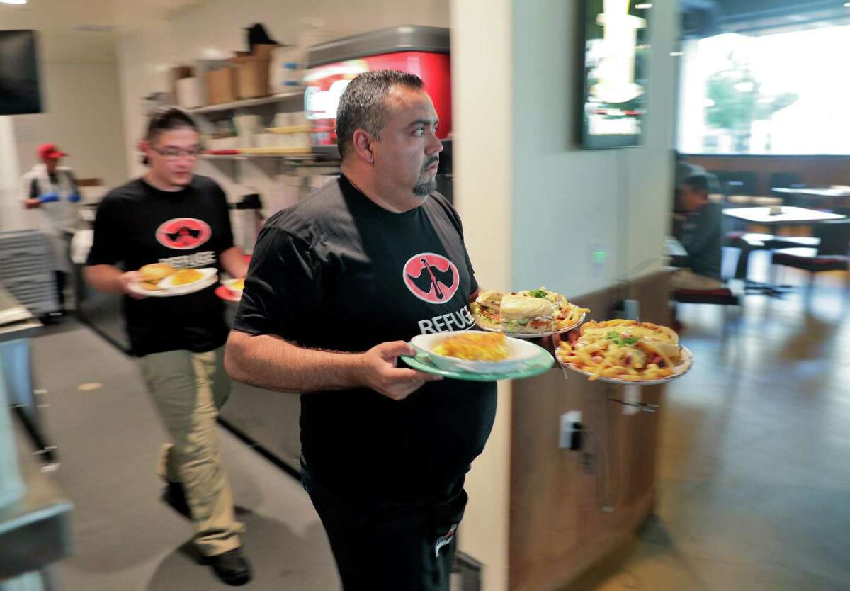 """Wait staff bring orders to diners at Refuge in San Mateo, where a new """"wellness"""" fee is covering increased labor costs."""