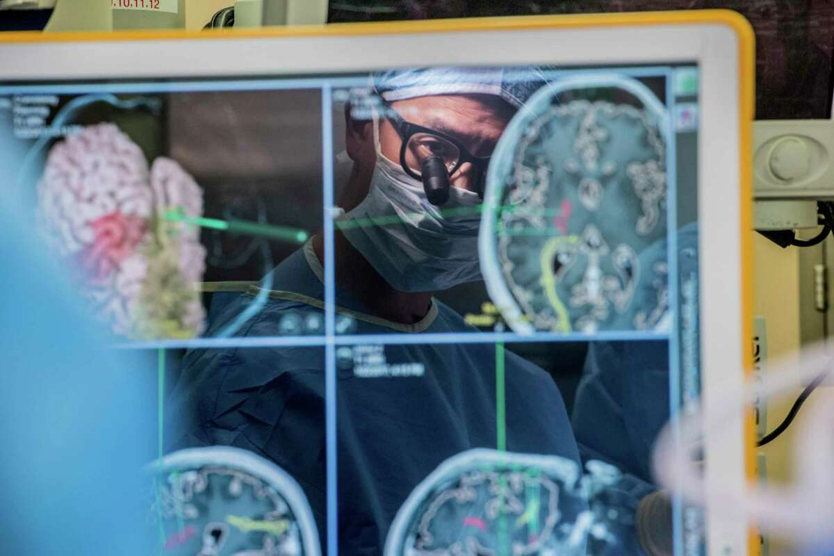 In this 2017 photo provided by the University of California, San Francisco, neurosurgeon Dr. Edward Chang is reflected in a computer monitor displaying brain scans as he performs surgery at UCSF. In a medical first, researchers, led by Chang, harnessed the brain waves of a man paralyzed and unable to speak for 15 years - and turned what he intended to say into sentences on a computer screen. (Barbara Ries/UCSF via AP)
