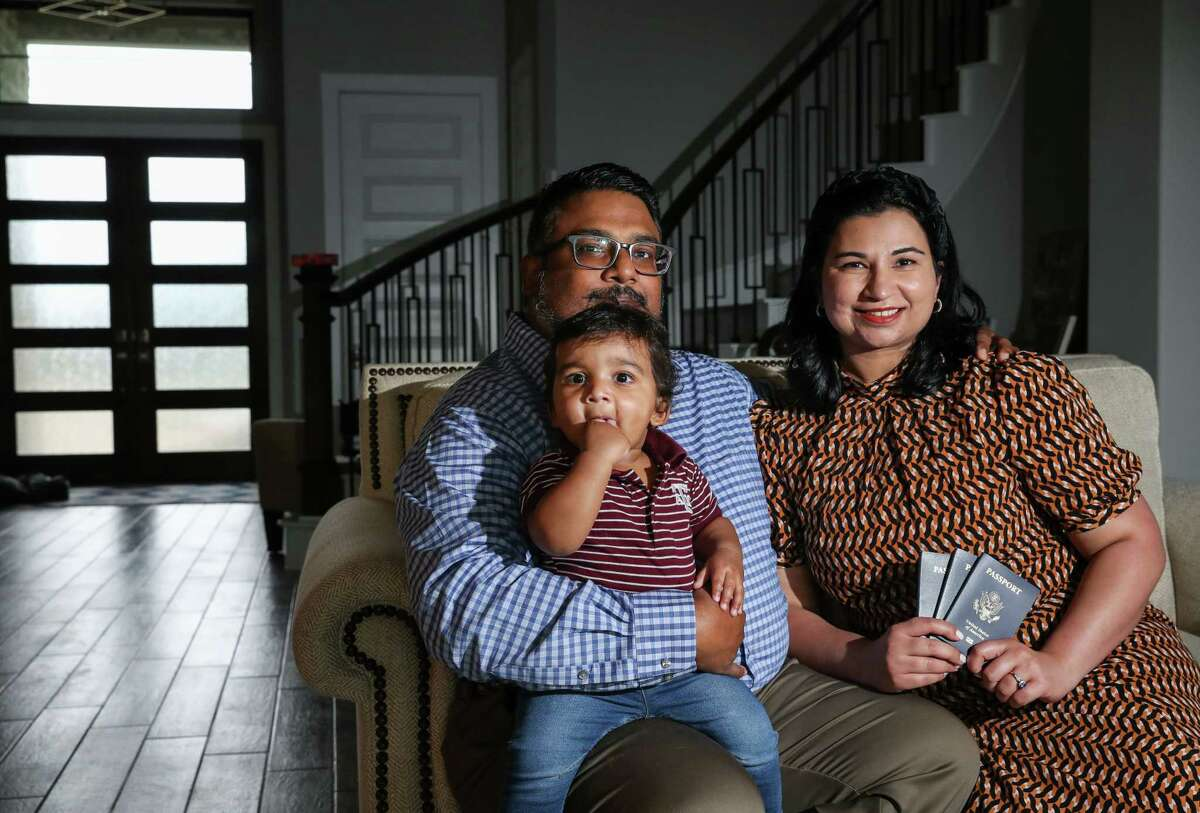Bryan John, from left, his son Malakai, 1, and his wife Poojan John pose for a portrait with their passports Wednesday, July 14, 2021, at their home in Cypress. The family had to cancel two trips to Mexico, one to visit family and the other for a wedding, because their Malakai's passport was delayed.