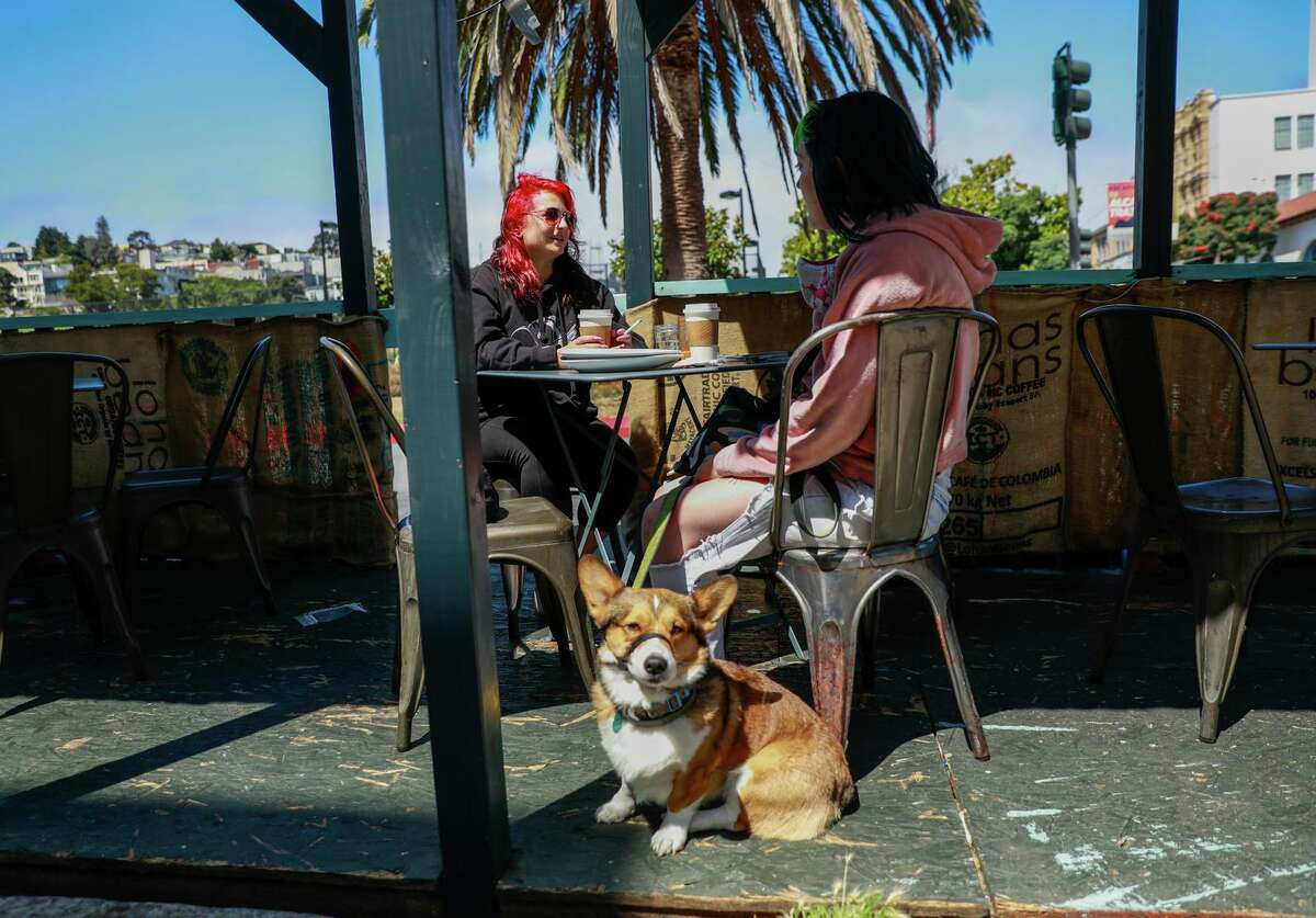 Cortney Garig (left) and Raegan Holder eat breakfast with Thor in the parklet outside of Dolores Park Cafe.