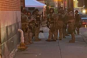 Police are seen putting on tactical gear before facing  Black Lives Matter protesters on Broadway in Saratoga Springs the evening of July 14, 2021.