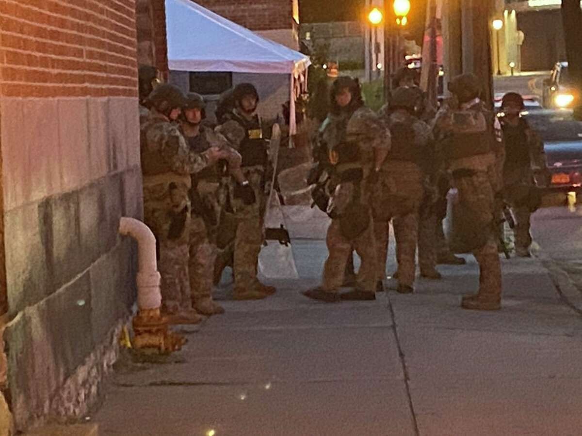Police are seen putting on tactical gear before facing Black Lives Matter protesters on Broadway in Saratoga Springs on the evening of Wednesday, July 14, 2021.