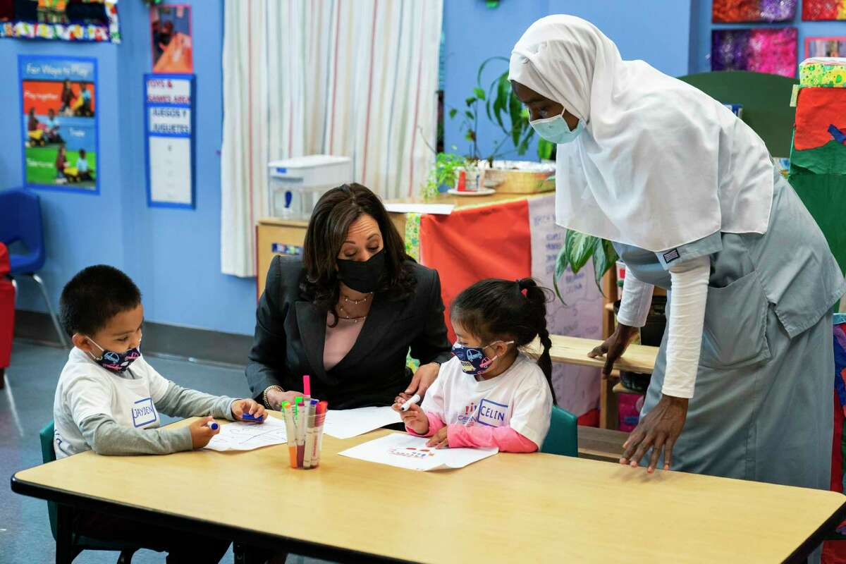 FILE - In this June 11, 2021, file photo, Vice President Kamala Harris talks with bilingual early childhood education school CentroNia students Jayden Bello, left, and Celina Barrera during a visit to the school in northwest Washington. Teacher Billo Diawara, right, watches.