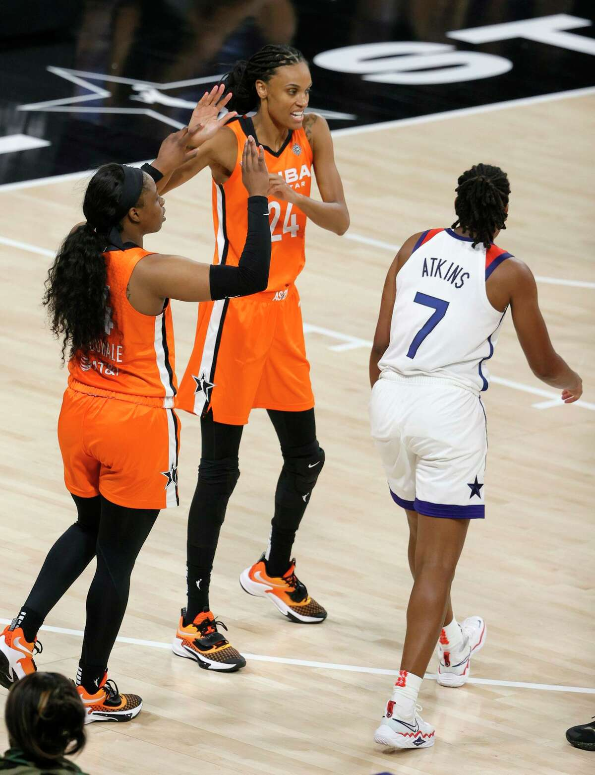 Arike Ogunbowale (left) and DeWanna Bonner of Team WNBA celebrate on the court after Ogunbowale hit a 3-pointer and was fouled by Ariel Atkins of the U.S. women's Olympic team.