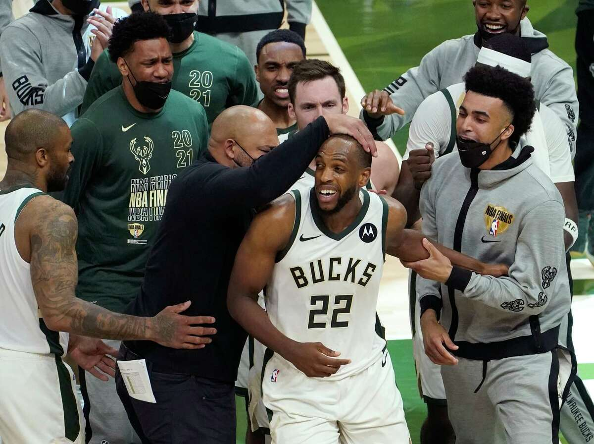Khris Middleton (22), who scored 10 straight points in the second half, is congratulated by his Milwaukee Bucks teammates in their win over the Phoenix Suns in Game 4 of the NBA Finals.