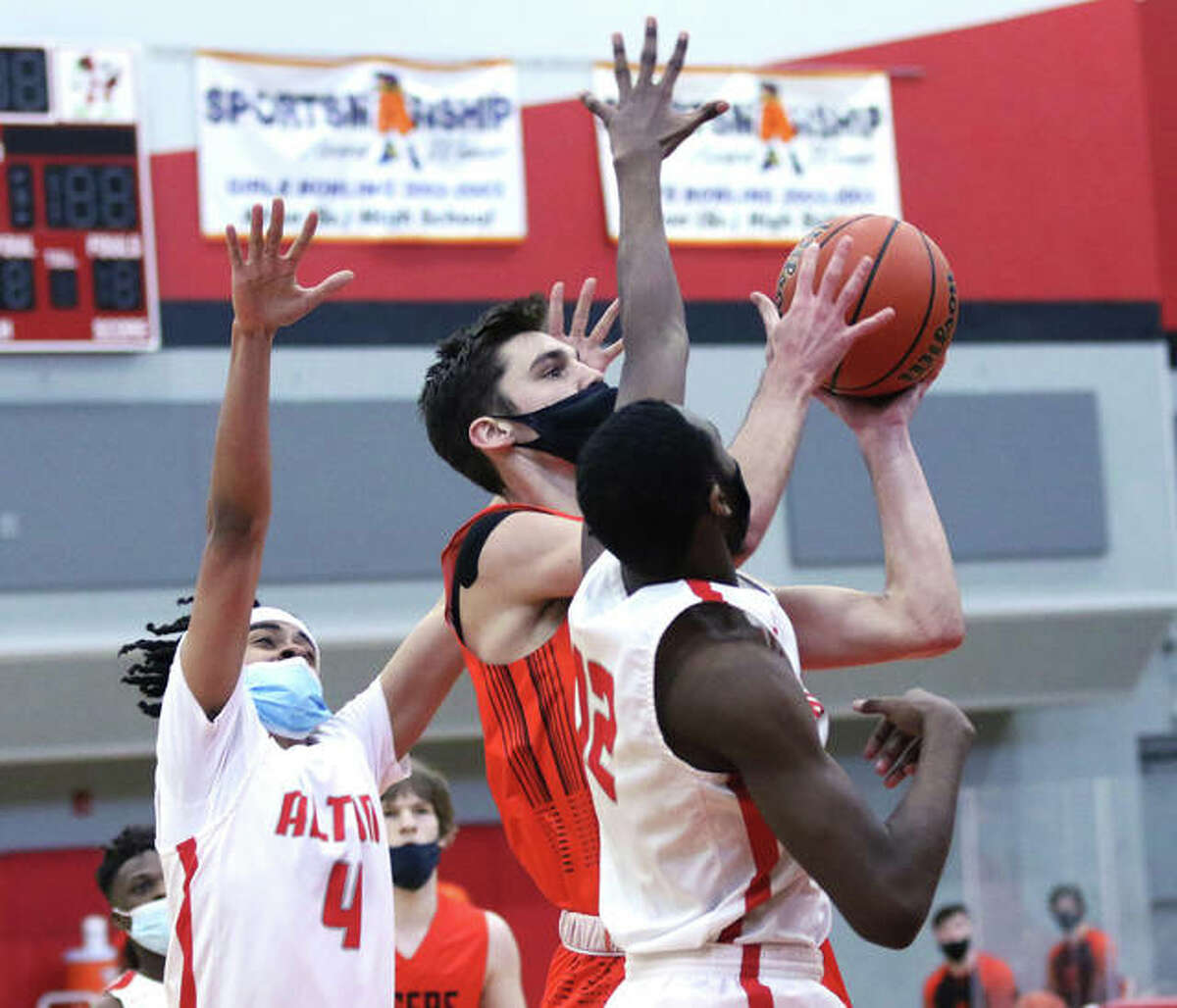 Edwardsville senior Brennan Weller (middle) puts up a shot between two Alton defenders during a SWC game last season at Alton High in Godfrey. Weller is the 2021 Telegraph Large-Schools Boys Basketball Player of the Year. He also won the award as a junior.