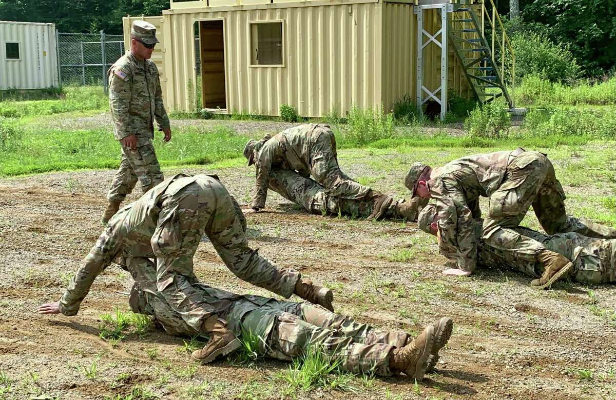 First Sgt. Rafael Navarro supervises officer candidates practicing the neck drag, a technique used to move wounded soldiers in combat.