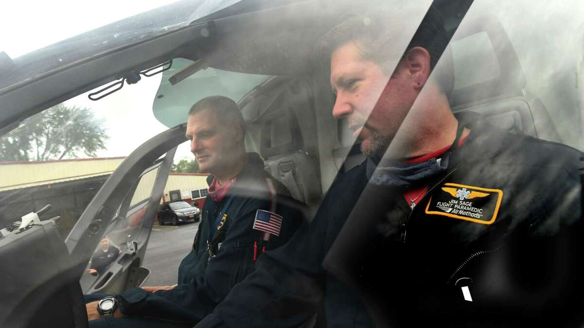 Air Methods (LifeNet) pilot Ben Davenport, left, and paramedic Jim Sage are seen in an air ambulance helicopter at the South Albany Airport on Friday, July 9, 2021 in Selkirk, N.Y. (Lori Van Buren/Times Union)