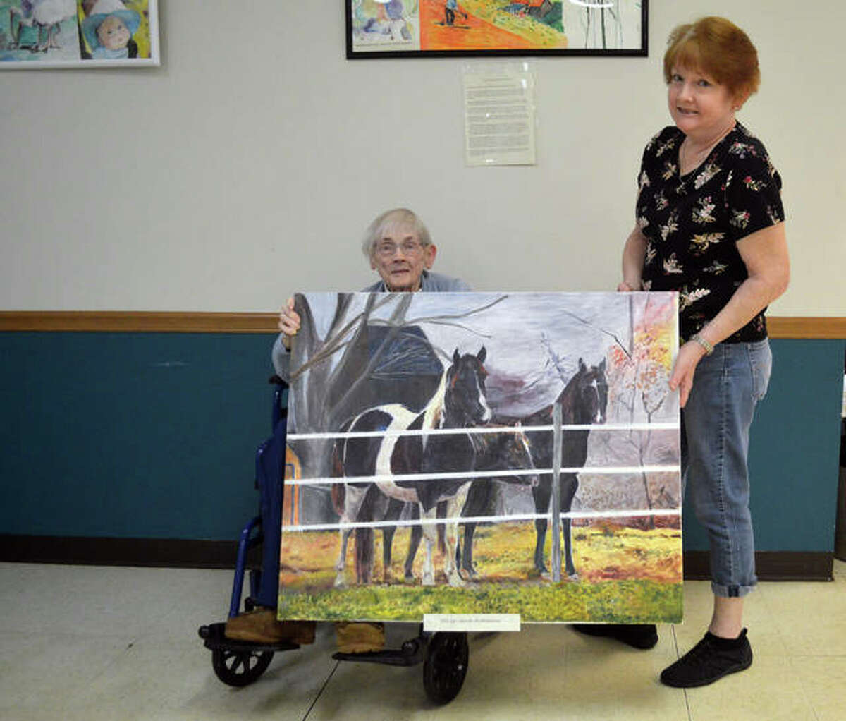 Carole Anne (Davis) Kotkiewicz, left, and her daughter, Lin Dillier, with one of the paintings by the 83-year-old Kotkiewicz that are now on display at Main Street Community Center.