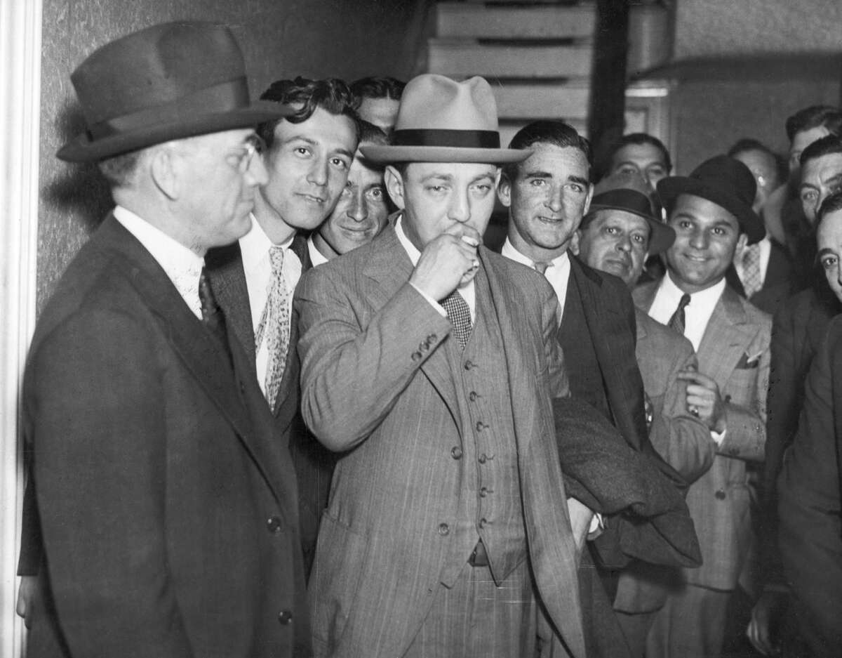 """Dutch Schultz, a bootlegger and racketeer, is shown here smoking a cigarette in front of New York Federal Court in 1935. Schultz's crimes infiltrated into labor unions from the early 1930s until his death. """"He was the first mobster that was a mainstay of organized crime,"""" said historian John Conway. """"He made money by extorting the unions."""""""