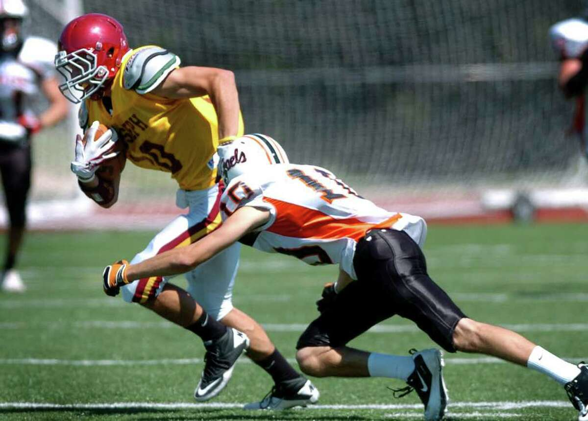 St. Joseph's Pat Mulligan avoids a tackle by Shelton's Stephen Leopold during their scrimmage Saturday September 4, 2010 at St. Joseph High School in Trumbull.