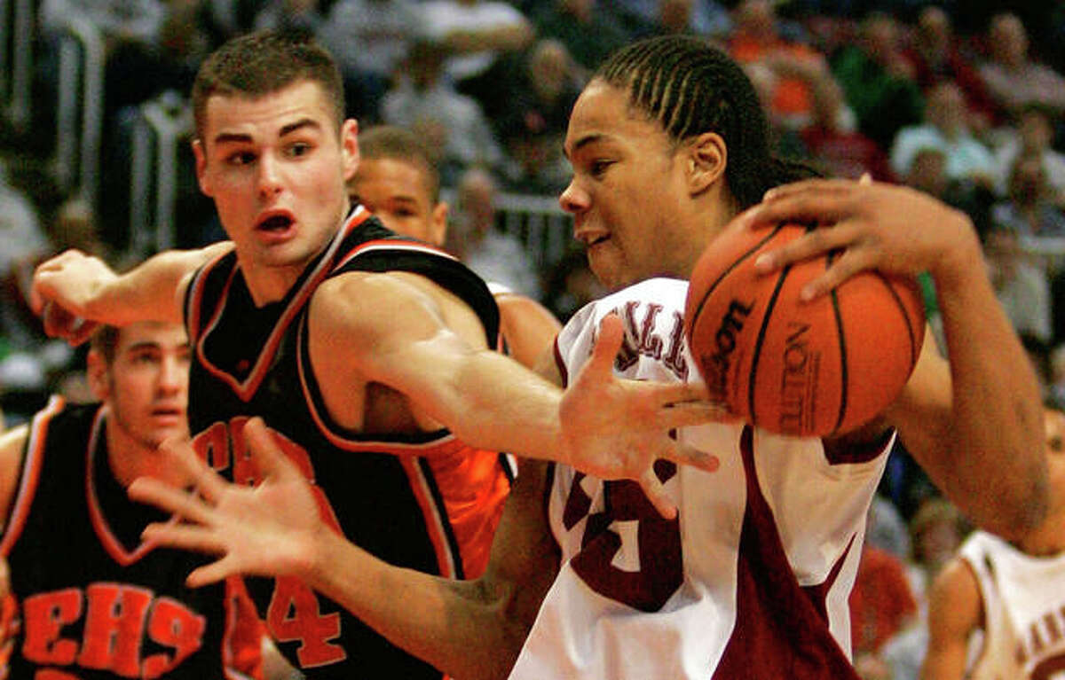 Edwardsville's Dustin Maguire, left, reaches in on Marshall's Ryan Hare during the fourth quarter of the quarterfinals of the IHSA boys' Class AA state basketball tournament in Peoria, Ill., Friday, March 17, 2006.