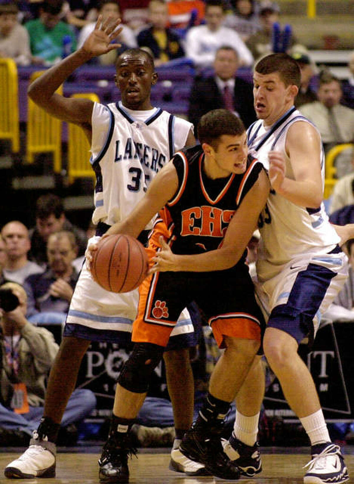 Edwardsville's Dustin Maguire passes around Belleville (Ill.) East's Marty McCoy, left, and Eric McCrary, right, at the annual High School Shootout, Wednesday, Dec. 7, 2005, in St. Louis.